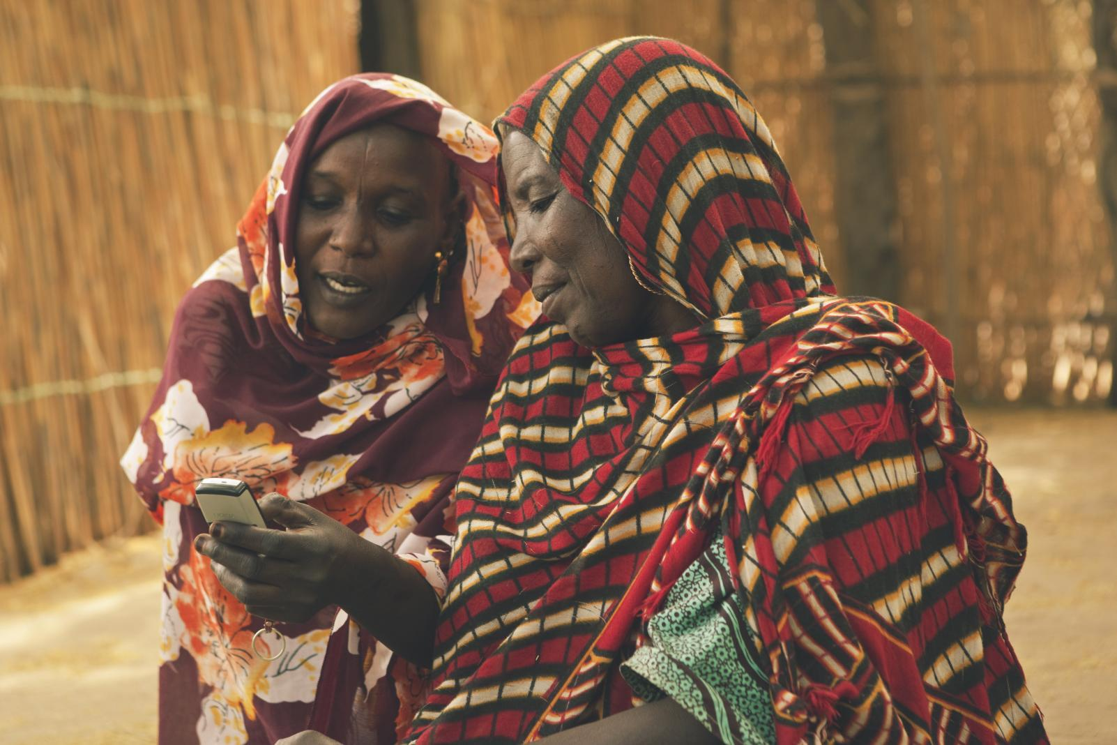 Women use a mobile phone, on Île de Fitiné, an island and fishing village in Lake Chad, Lac Region