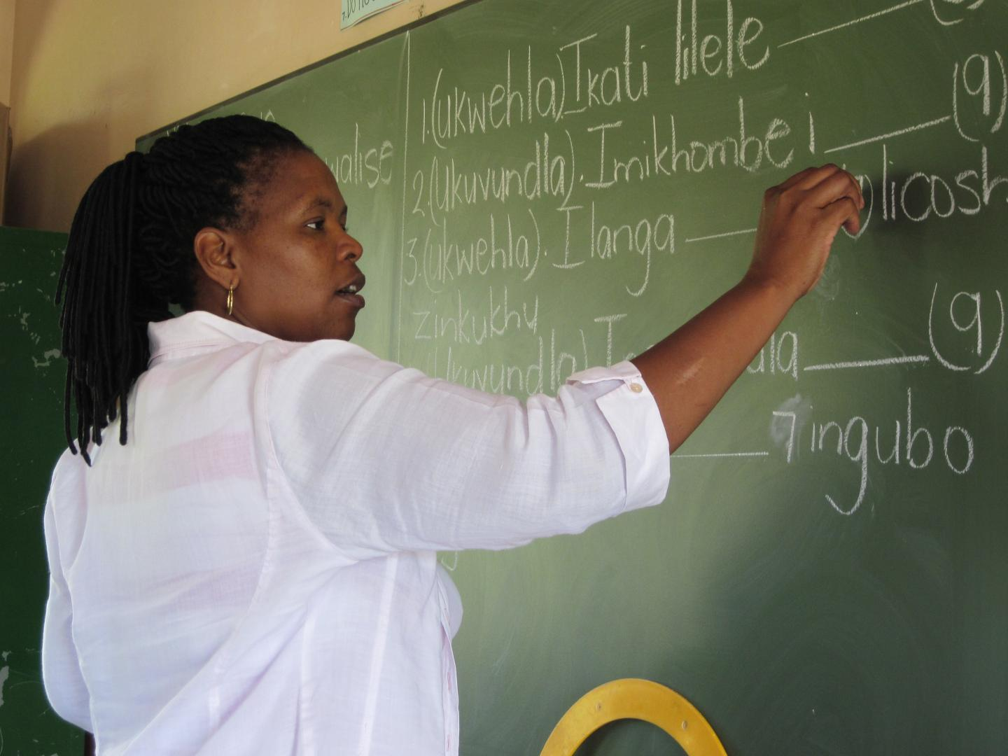 Child's View – Ms. Zondi, a teacher, writes on the chalkboard during a seventh grade Zulu language class