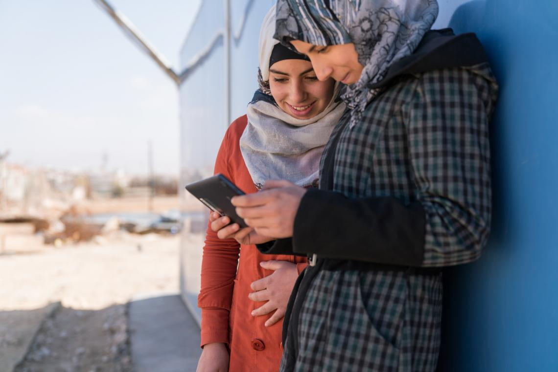 Two adolescent girls use a cellphone outside a solar kiosk in the Za'atari camp for Syrian refugees,